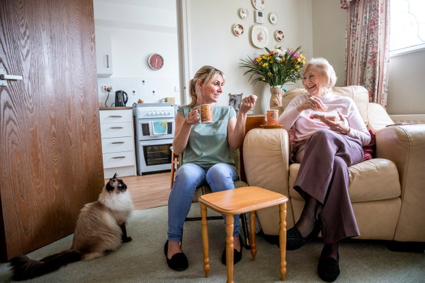 Senior woman sitting in her armchair listening to a younger woman talking. Both look happy as they enjoy a drink and snack together