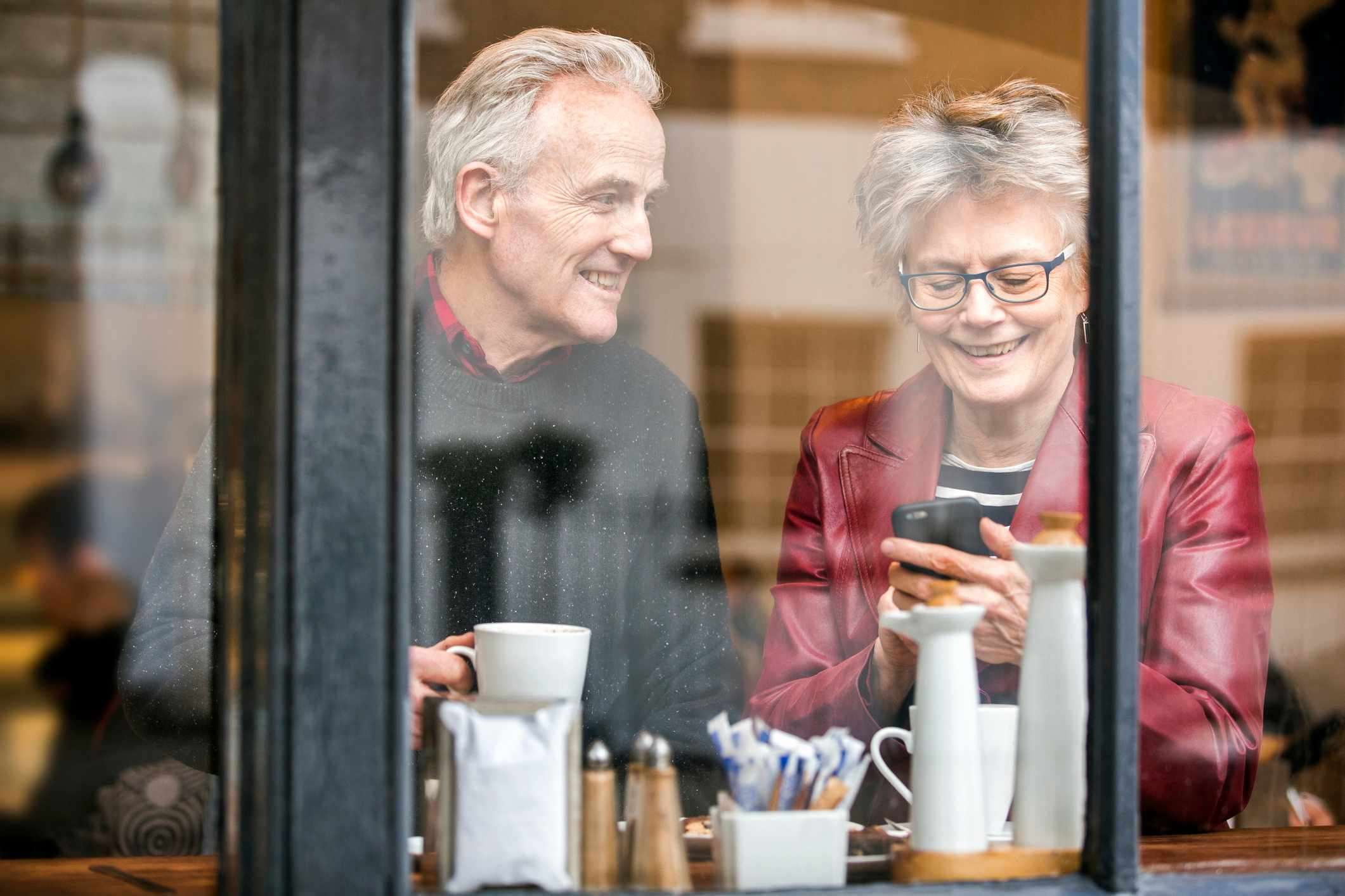 Senior couple in cafe window seat drinking coffee and texting on smartphone