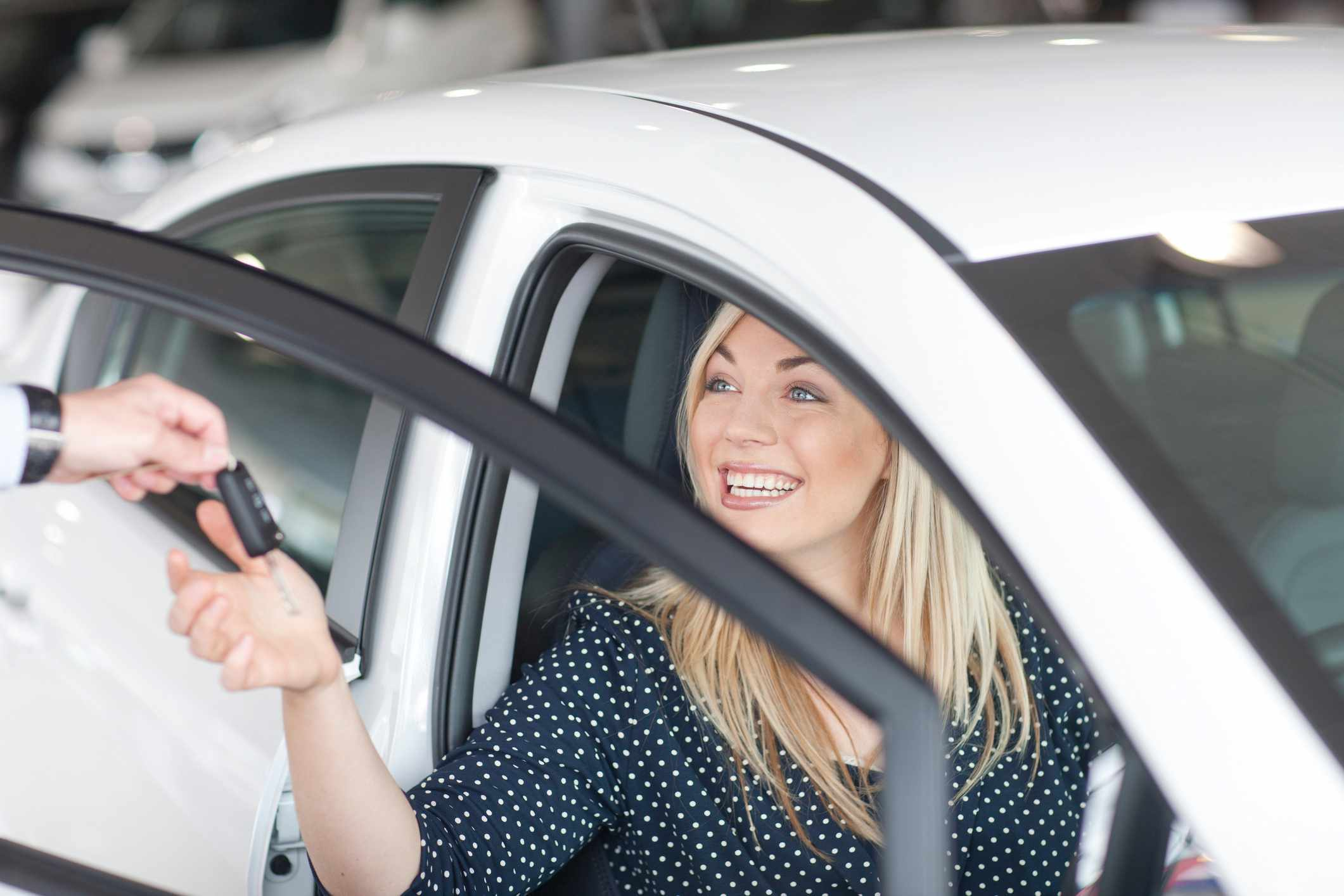 Young woman sitting in new car with key in showroom