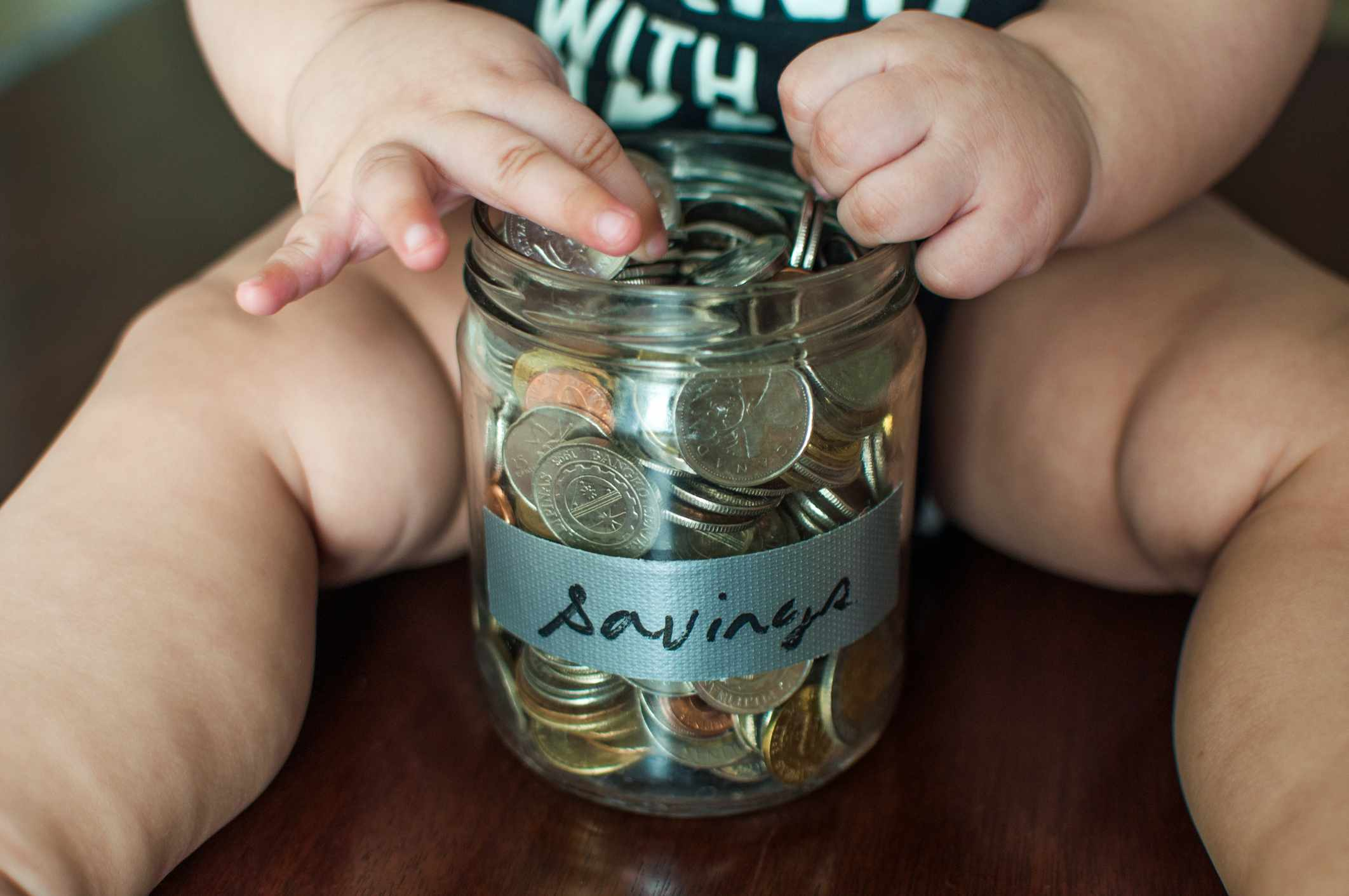 A financial concept wherein a baby boy is holding a jar filled with coins