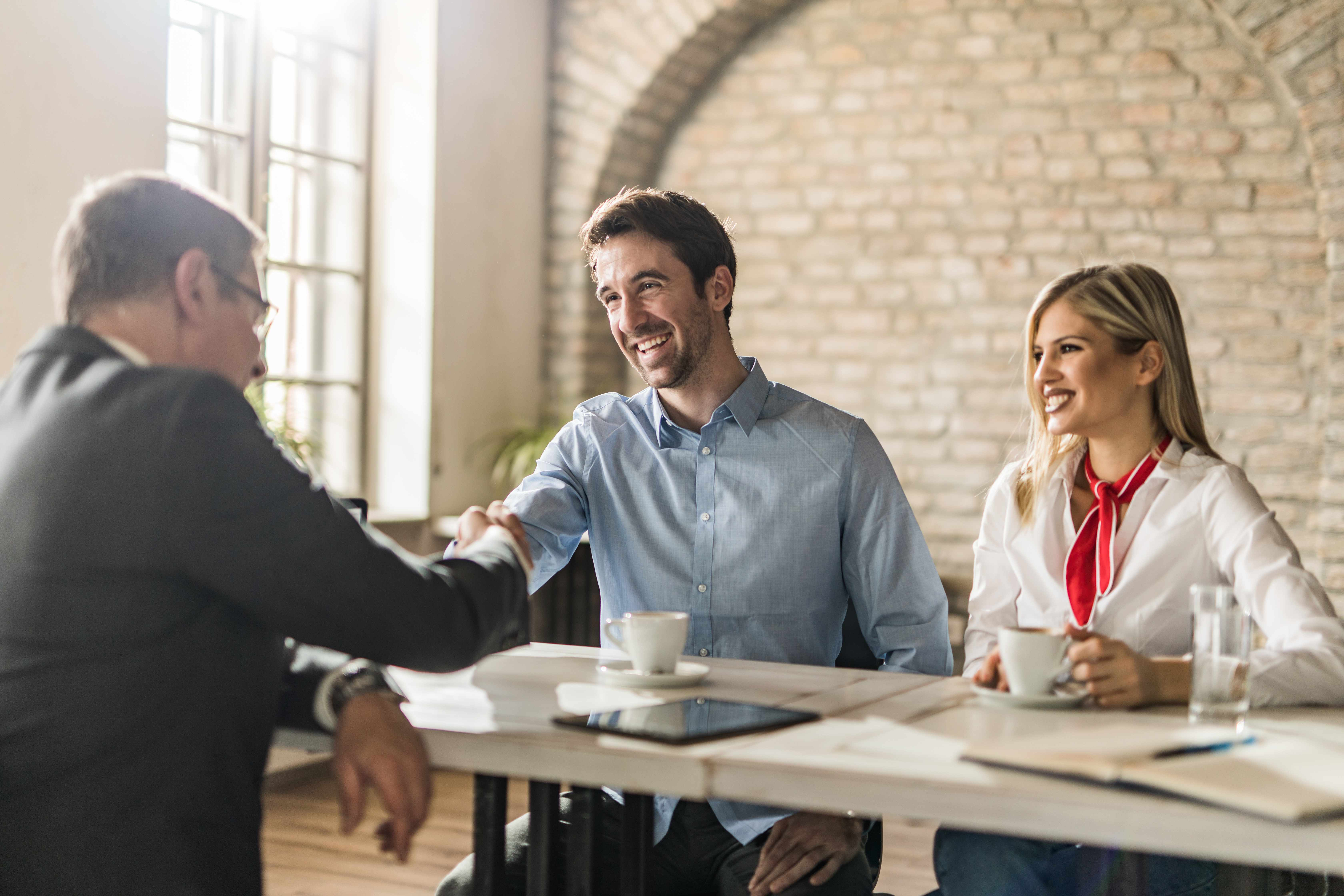 Young happy couple came to an agreement with their insurance agent on a meeting in the office. Focus is on young man shaking hands with agent.