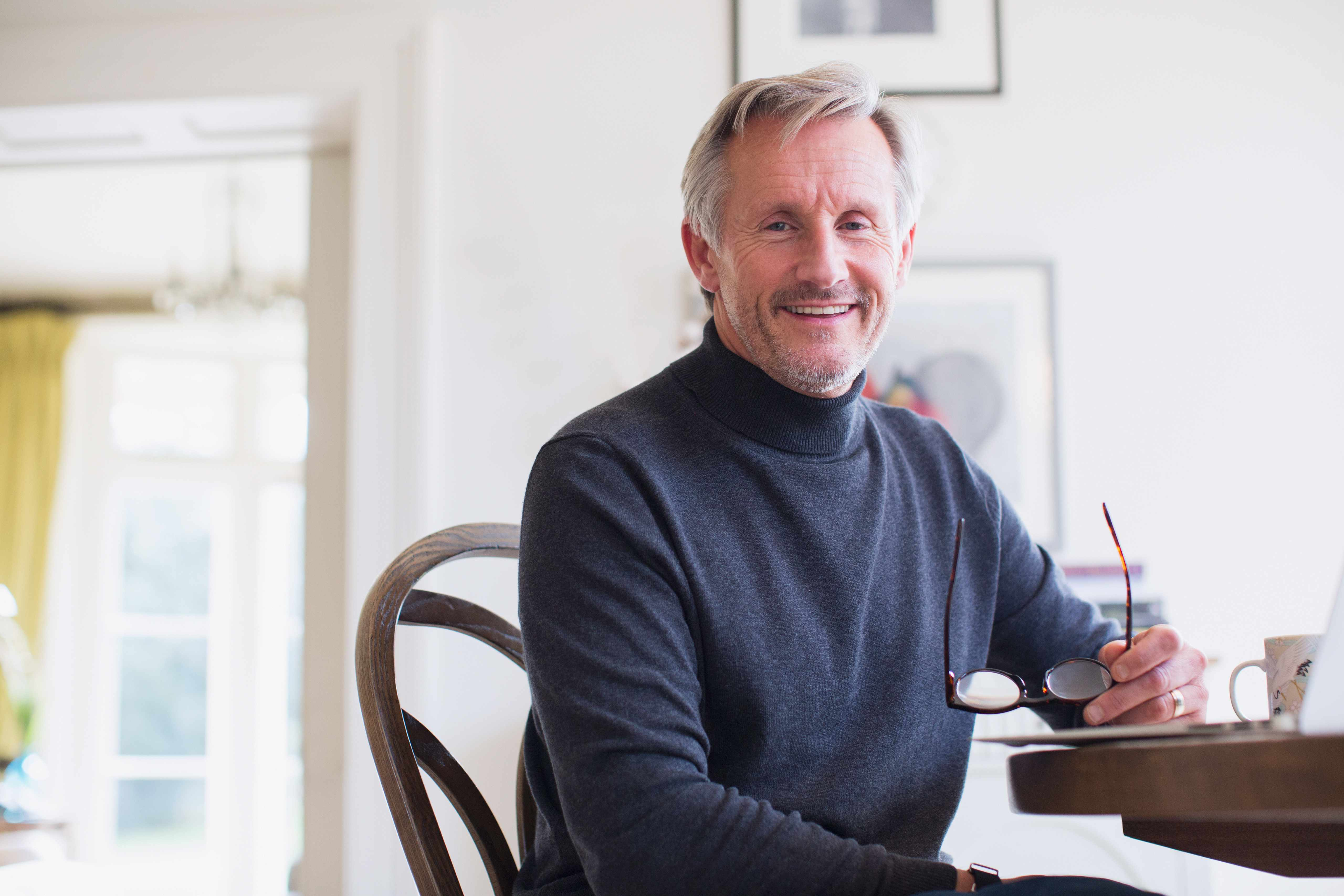 Portrait smiling mature man at dining table