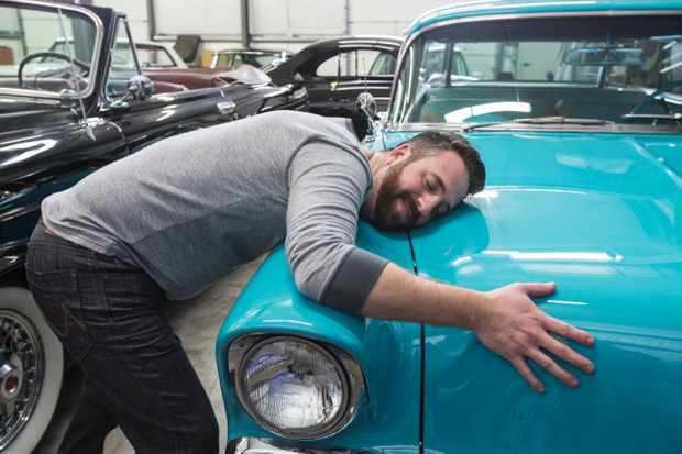 A caucasian male hugging the hood of his old sedan in a classic car repair shop.