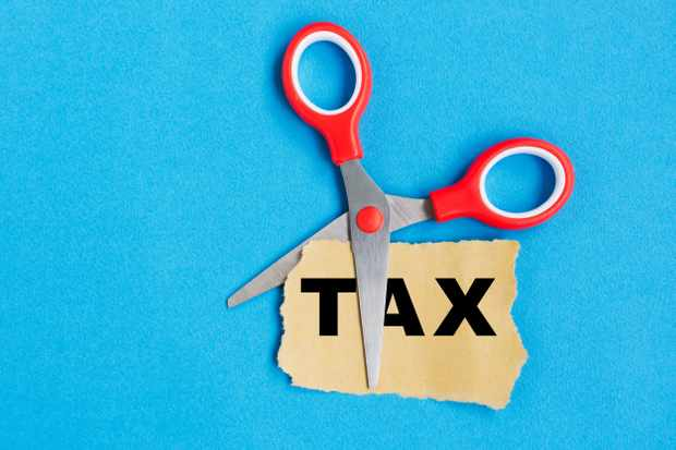 Tax word on paper cut by scissor, blue background.