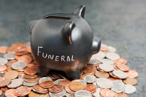 "A coin piggy-bank with ""Funeral"" written on it sitting on a pile of coin."