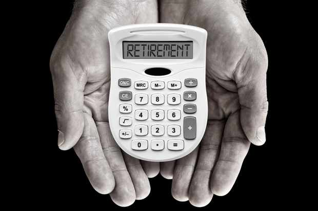 Calculator in hands with the word retirement
