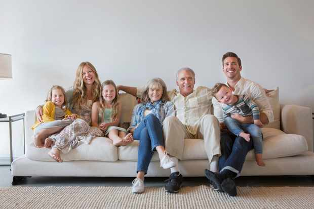 Caucasian multi-generation family sitting on sofa in living room