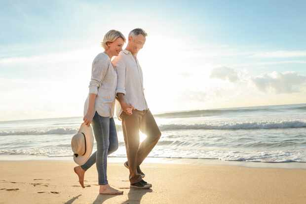 Mature couple walking on the beach at sunset or sunrise. They are having fun, laughing and smiling. The man has grey hair. Ocean in the background. Back lit with lens flare.
