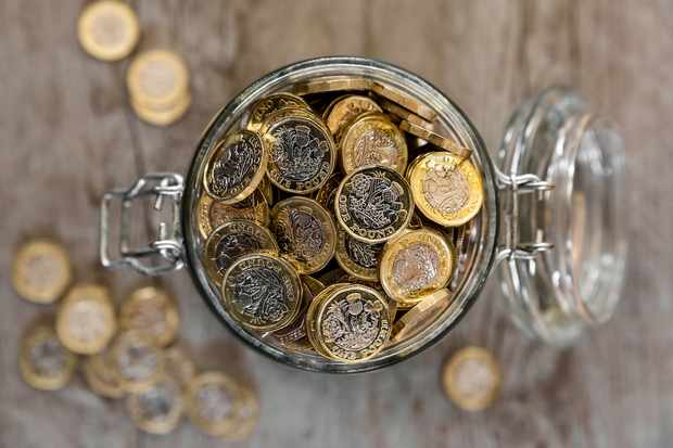 A jar full of saved one pound coins.