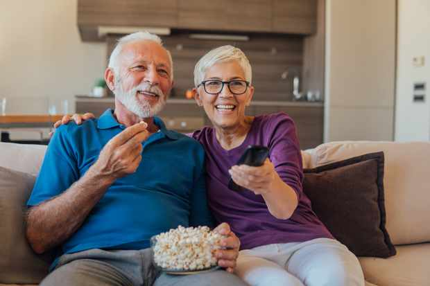 Elderly couple eating popcorn and watching TV together
