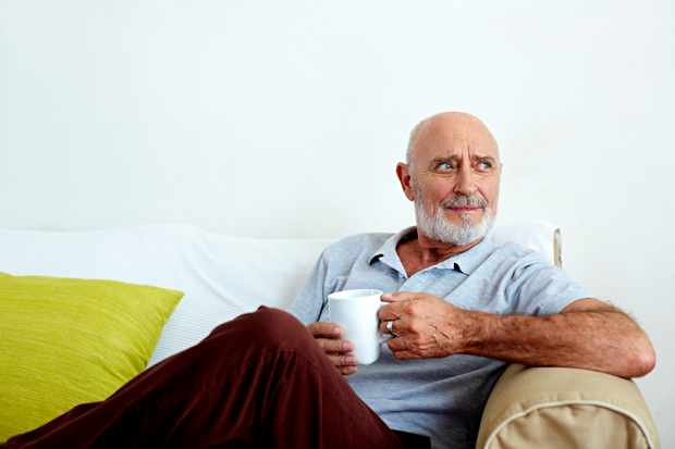 Thoughtful senior man holding coffee mug while relaxing on sofa at home