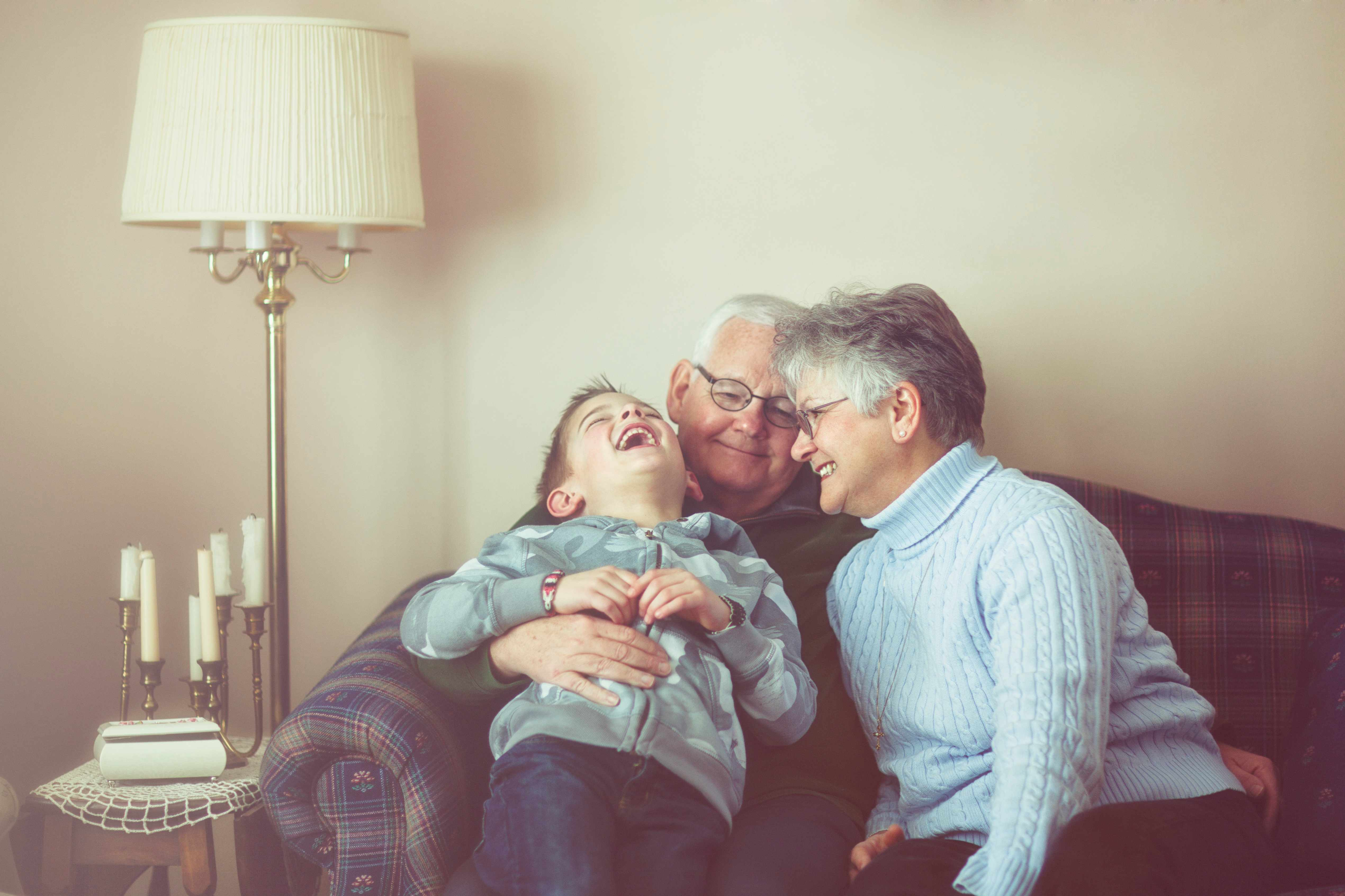 Grandmother, grandfather and grandson laughing together.