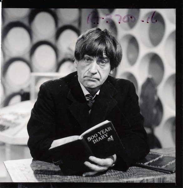 Shot number RT 3700 16. The Doctor in the Tardis with his 500 Year Diary. Here you might spot Patrick Troughton has flecks of sawdust or Jablite polystyrene in his hair and on the shoulders of his jacket. He's again concealing his injured right hand.