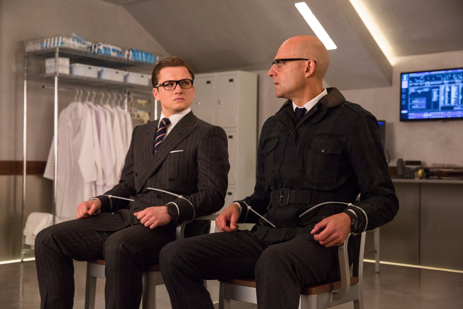 Taron Egerton and Mark Strong tied to chairs