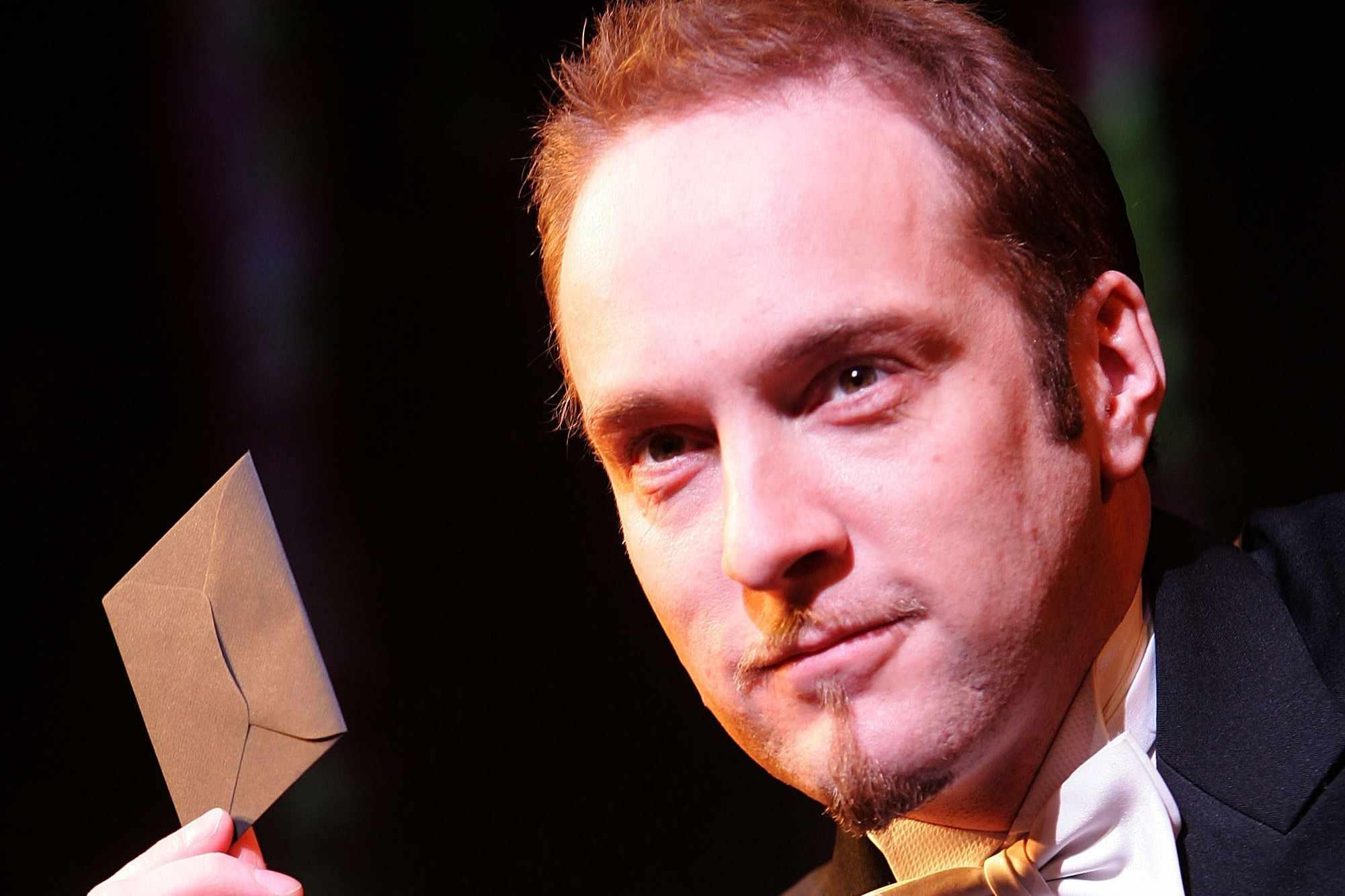 Derren Brown holding a letter