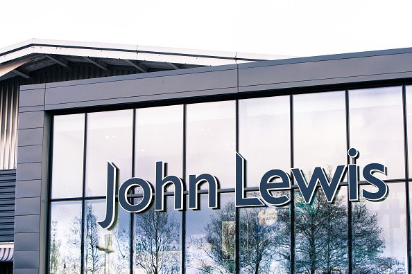 The John Lewis name is displayed on the facade of the department store, with trees reflected in the glass of the store front, in High Wycombe, England.
