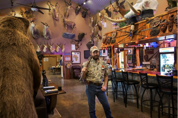 Philip Glass, a Texan Big Game Hunter, poses in a trophy room (BBC, TL)