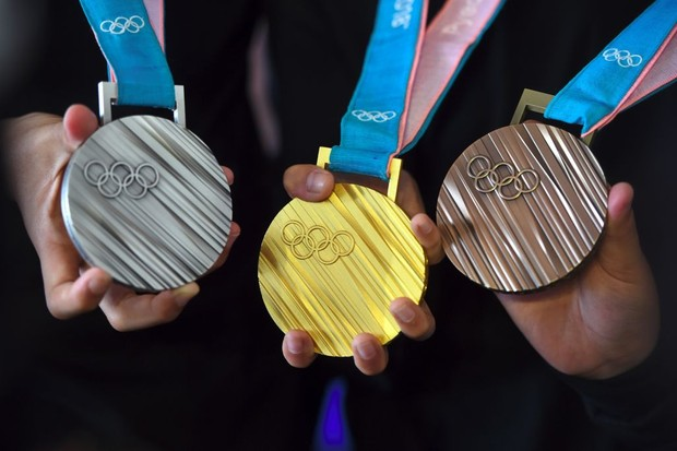 The PyeongChang 2018 Olympic medals are displayed by young South Korean athletes during their unveiling at a ceremony in Seoul on September 21, 2017. The Olympic Winter Games PyeongChang 2018 medals were officially unveiled on September 21, with features of the Korean alphabet consonants on their bodies. / AFP PHOTO / JUNG Yeon-Je        (Photo credit should read JUNG YEON-JE/AFP/Getty Images)