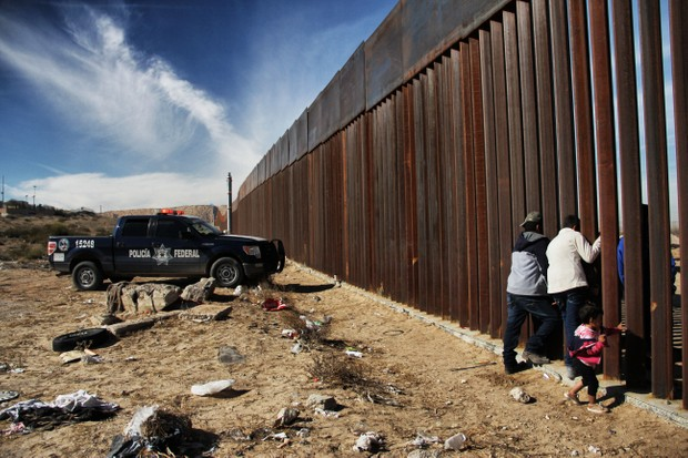 Members of a family meet through the border wall between Mexico and the United States (Getty)
