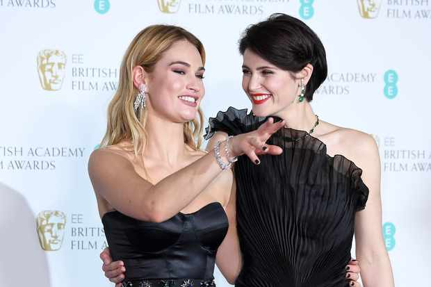 Lily James and Gemma Arterton pose in the press room during the EE British Academy Film Awards (BAFTA) held at Royal Albert Hall on February 18, 2018