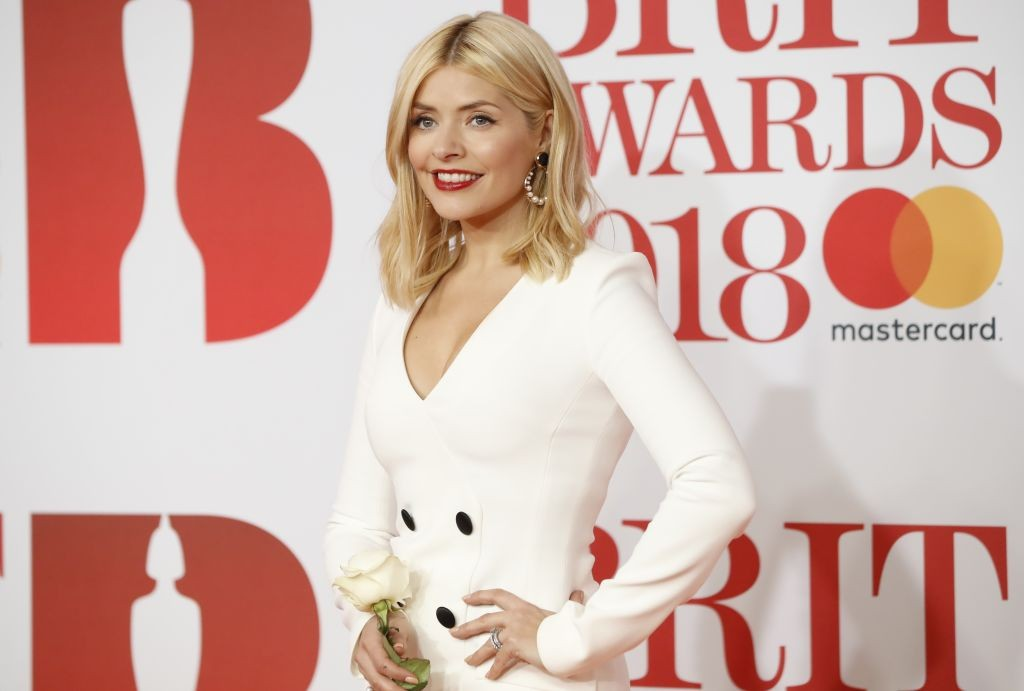 British television presenter Holly Willoughby poses on the red carpet on arrival for the BRIT Awards 2018 in London on February 21, 2018. / AFP PHOTO / Tolga AKMEN / RESTRICTED TO EDITORIAL USE  NO POSTERS  NO MERCHANDISE NO USE IN PUBLICATIONS DEVOTED TO ARTISTS        (Photo credit should read TOLGA AKMEN/AFP/Getty Images)