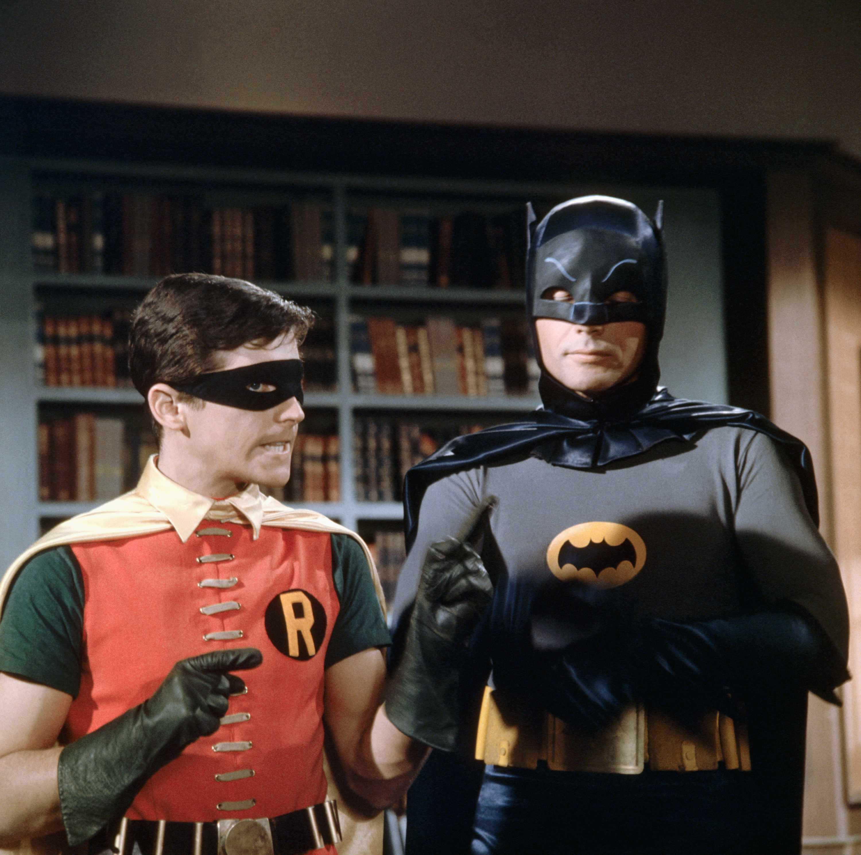Burt Ward (left) as Robin and Adam West as Batman discuss their next move against Gotham City's supervillains on the set of the Batman television show (1966-1968).   Location: on the Batman set.