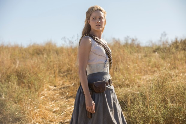 Dolores from Sky's Westworld, standing alone in a dry field with ammunition slung over her shoulder