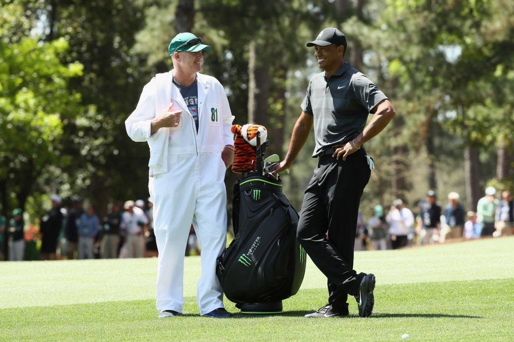 Tiger Woods of the United States and caddie Joe LaCava wait on the ninth hole during the first round of the 2018 Masters Tournament at Augusta National Golf Club on April 5, 2018 in Augusta, Georgia.  (Photo by Jamie Squire/Getty Images)