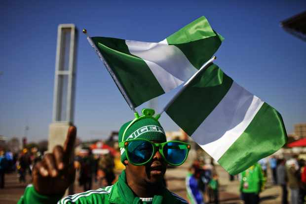 A football fan waves national flags og Nigeria as he arrives at Ellis Park stadium in Johannesburg for the 2010 World Cup match between Argentina and Nigeria on June 12, 2010. AFP PHOTO/GIANLUIGI GUERCIA (Photo credit should read GIANLUIGI GUERCIA/AFP/Getty Images)
