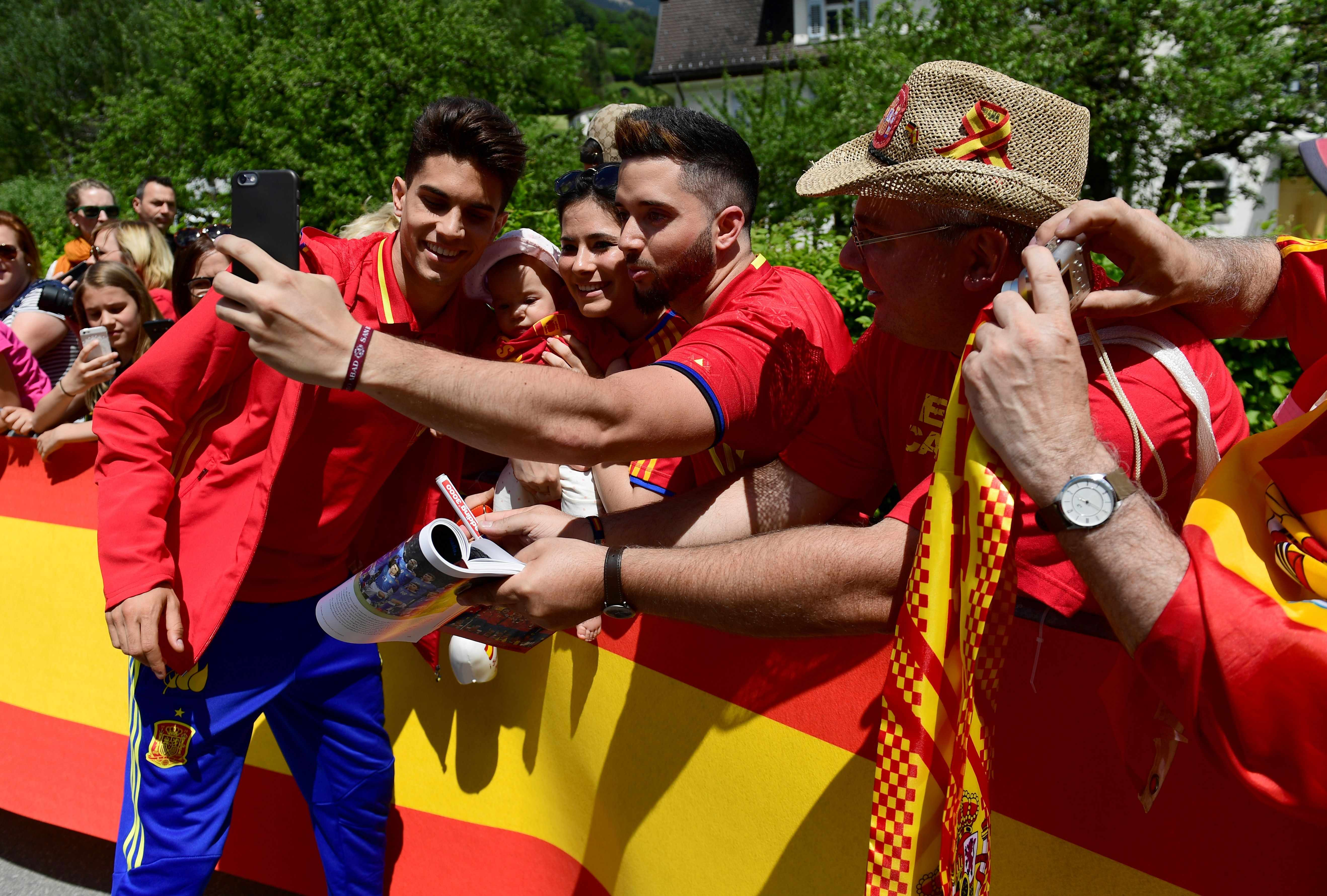 Spain's defender Marc Batra (L) poses with fans as he arrives at his hotel in Schruns on May 26, 2016 where the team will train for the upcoming Euro 2016 European football championships.     / AFP / PIERRE-PHILIPPE MARCOU        (Photo credit should read PIERRE-PHILIPPE MARCOU/AFP/Getty Images)