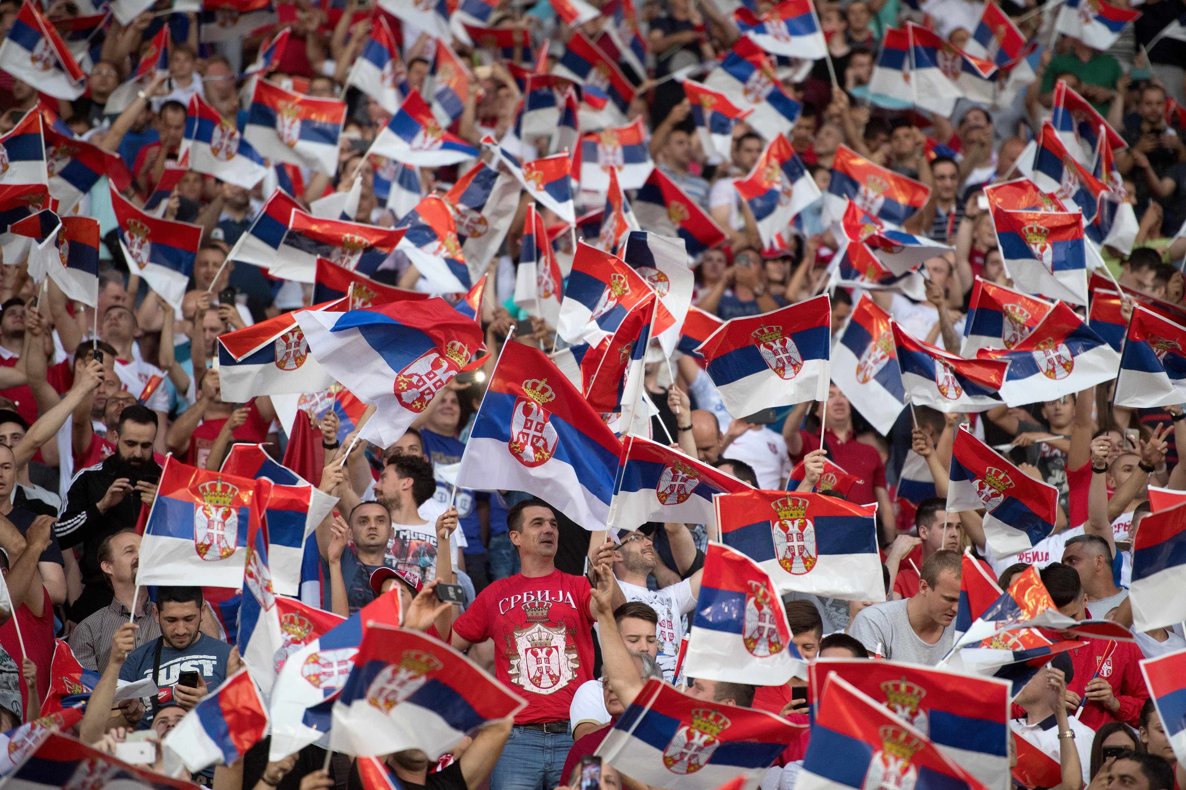 Serbian supporters wave national flags ahead of the WC 2018 football qualification match between Serbia and Wales in Belgrade on June 11, 2017.   / AFP PHOTO / ANDREJ ISAKOVIC        (Photo credit should read ANDREJ ISAKOVIC/AFP/Getty Images)