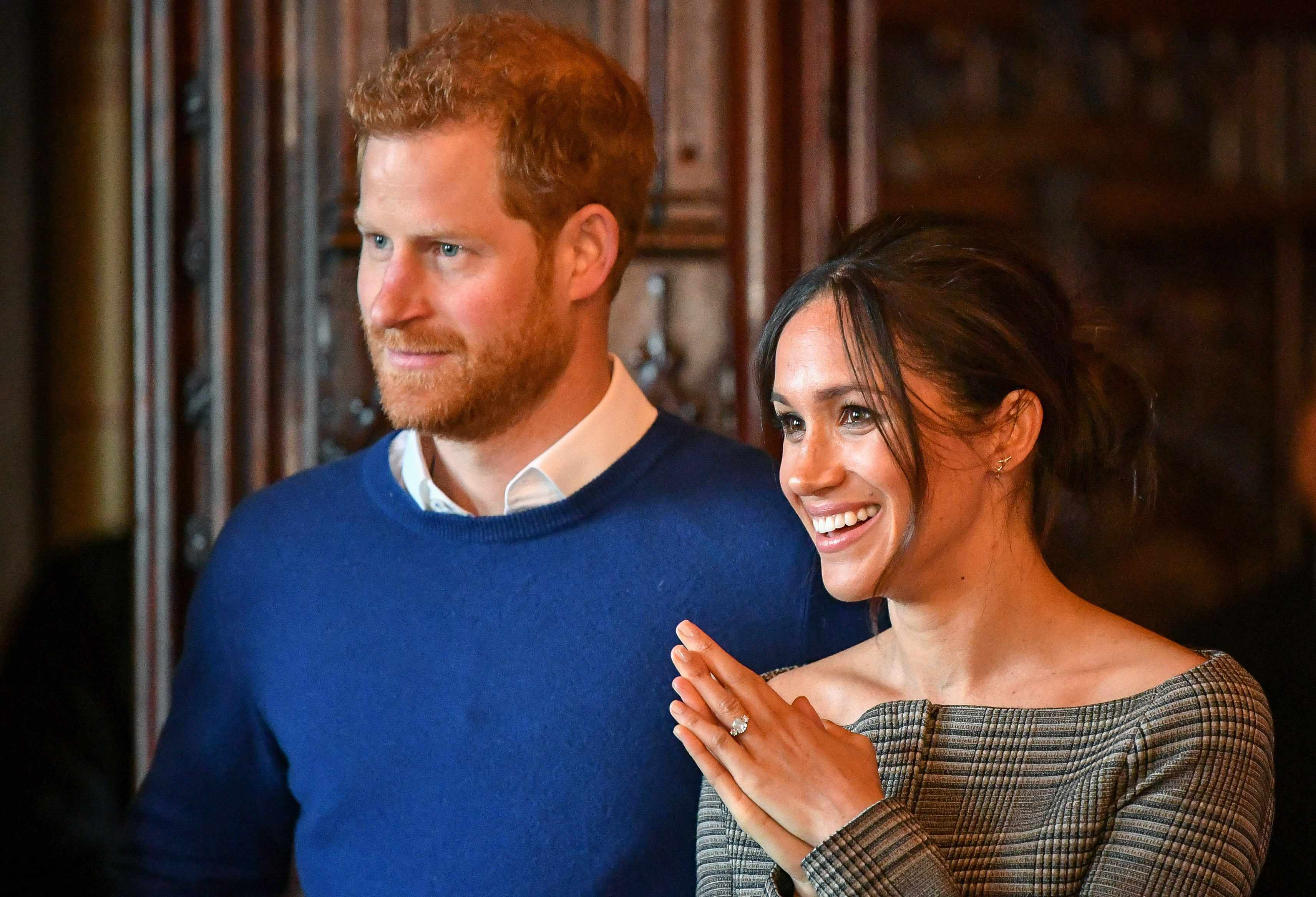 CARDIFF, WALES - JANUARY 18:  Prince Harry and Meghan Markle watch a performance by a Welsh choir in the banqueting hall during a visit to Cardiff Castle on January 18, 2018 in Cardiff, Wales. (Photo by Ben Birchall - WPA Pool / Getty Images)  TL