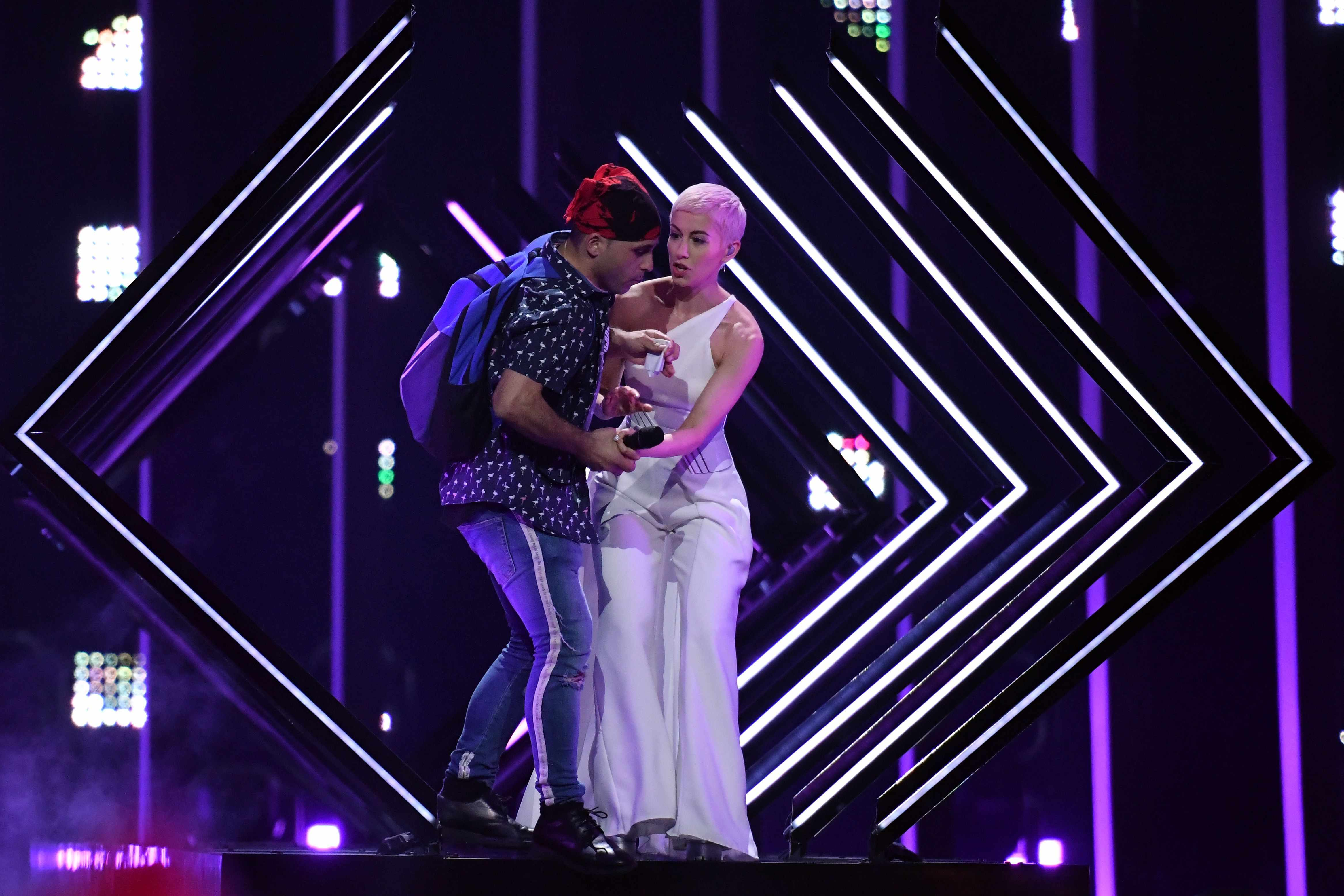 """A man takes the microphone from Britain's singer Susanna Marie Cork aka SuRie as she performs """"Storm"""" during the final of the 63rd edition of the Eurovision Song Contest 2018 at the Altice Arena in Lisbon, on May 12, 2018. (Photo by Francisco LEONG / AFP)        (Photo credit should read FRANCISCO LEONG/AFP/Getty Images)"""