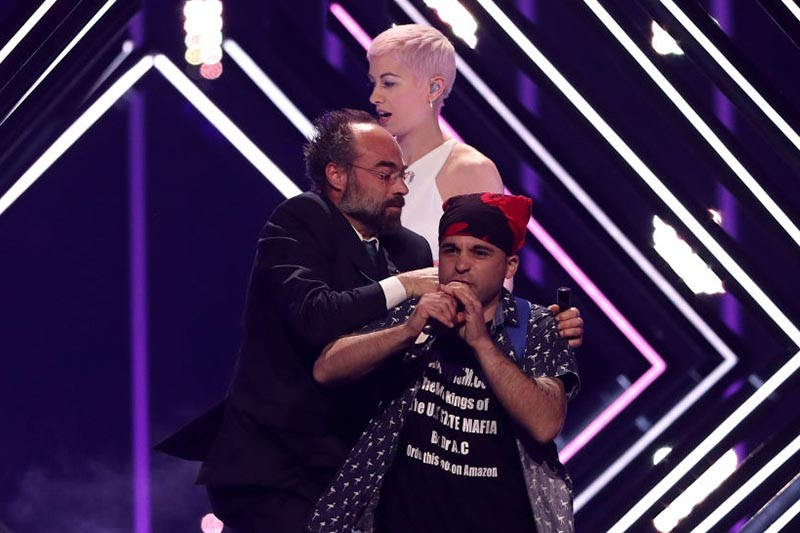 A man take the stage to interrupt singer SuRie of United Kingdom performs during the 2018 Eurovision Song Contest Grand Final, at the Altice Arena in Lisbon, Portugal on May 12, 2018. ( Photo by Pedro Fiúza/NurPhoto via Getty Images, HF)