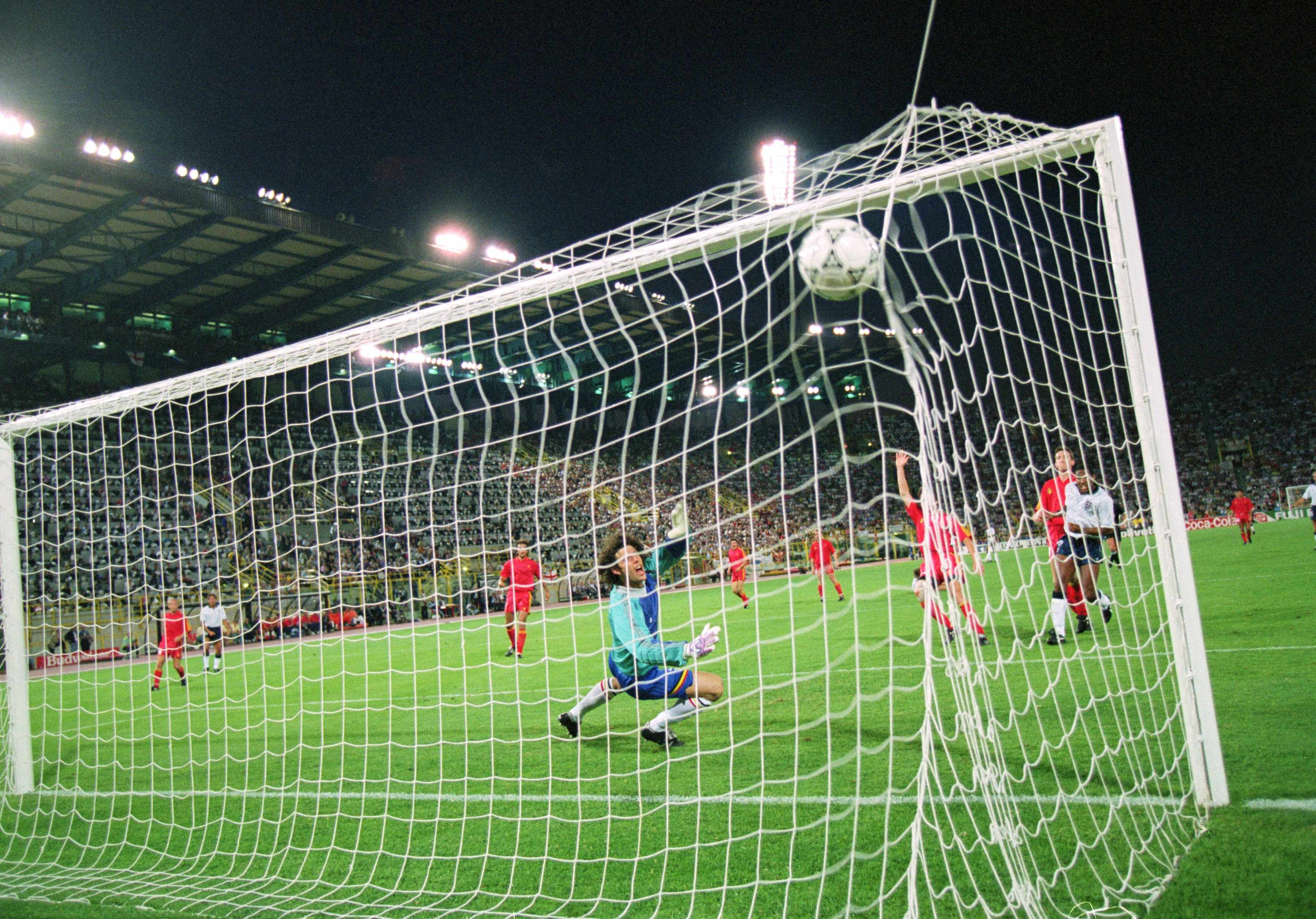 26 Jun 1990:  John Barnes of England (L) shoots past Michel Preud'homme of Belgium, but the goal is ruled out for offside during the FIFA World Cup Finals 1990 second round match against Belgium played at the Dall''Ara Stadium, in Bologna, Italy. England won the match 1-0 after extra-time.  Mandatory Credit: David Cannon /Allsport