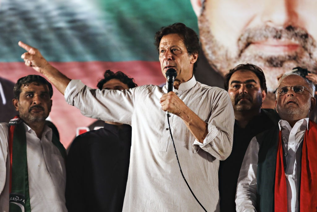 Imran Khan, chairman of Pakistan Tehreek-e-Insaf (PTI), also known as Movement for Justice, center, speaks during a campaign rally in Lahore, Pakistan, on Friday, July 20, 2018. Whoever wins Pakistan's election next week, gains in the rupee, stocks and bonds are likely to be short-lived as the new government grapples with a mounting set of economic challenges. Photographer: Asad Zaidi/Bloomberg via Getty Images