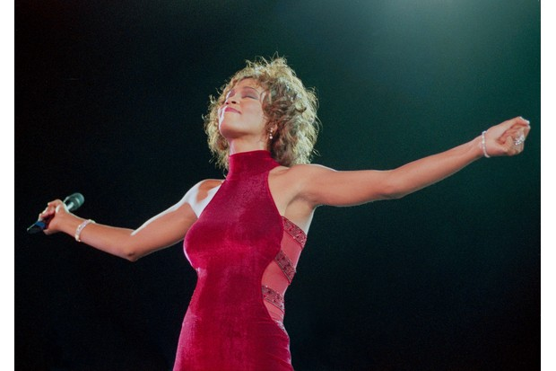 Whitney Houston performs on stage in 1996. (Photo by Phil Dent/Redferns)