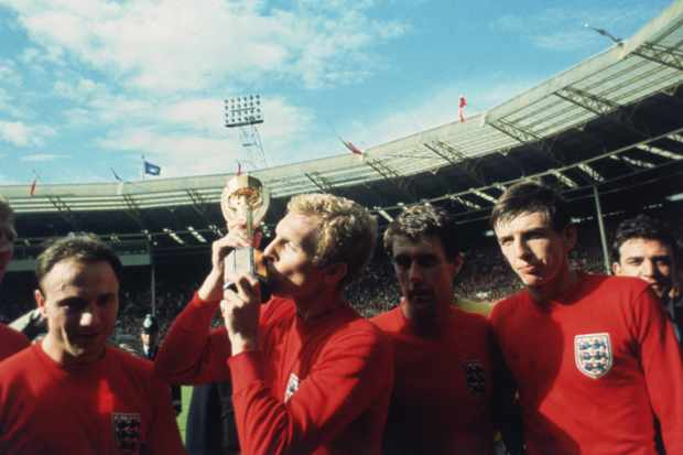 England captain Bobby Moore kissing the Jules Rimet trophy as the team celebrate winning the 1966 World Cup final against Germany at Wembley Stadium. His team mates are, left to right, George Cohen, Geoff Hurst and Martin Peters, 30th July 1966. (Photo by Hulton Archive/Getty Images)