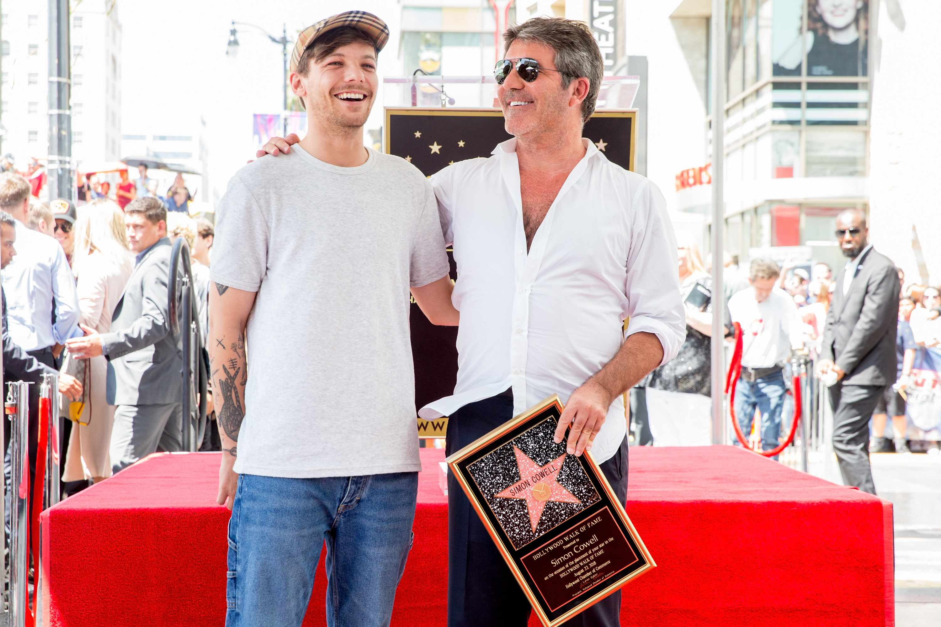 HOLLYWOOD, CA - AUGUST 22:  Louis Tomlinson (L) and Simon Cowell attend a ceremony honoring Cowell with a star on the Hollywood Walk of Fame on August 22, 2018 in Hollywood, California.  (Photo by Rich Fury/Getty Images) TL