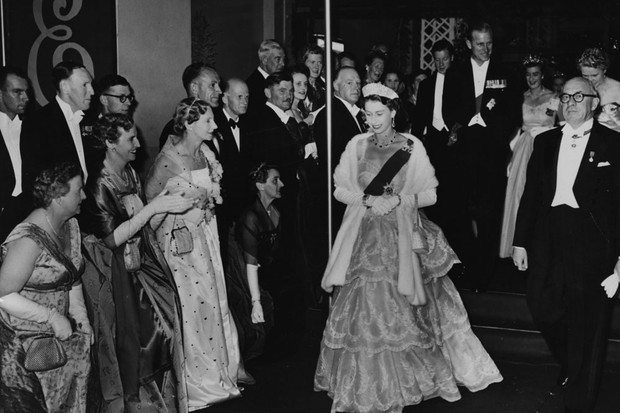 Queen Elizabeth II and the Duke of Edinburgh (behind) wearing formal dress as they leave City Hall following a Civic Ball, Hobart, circa 1954. (Photo by Fox Photos/Hulton Archive/Getty Images)