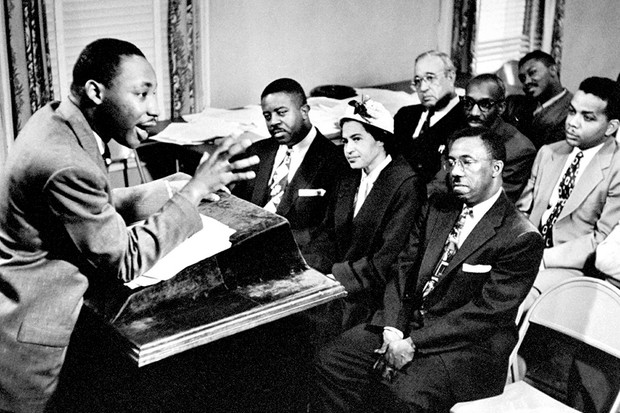 Rev. Martin Luther King, director of segregated bus boycott, discusses strategies with a team including Rosa Parks (front row) in 1956
