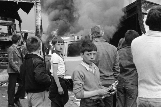 Children watch vehicles burn following rioting on the Lower Falls Road, Belfast. 17th September 1976. (Photo by Alex Bowie/Getty Images)