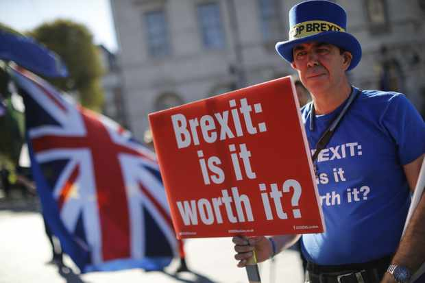 "Anti-Brexit campaigner Steve Bray stands outside parliament with EU and Union Flags and a placard that reads ""Brexit: is it worth it?"" as he protests in Parliament Square in London on October 9, 2018. (Photo by Tolga AKMEN / AFP)        (Photo credit should read TOLGA AKMEN/AFP/Getty Images)"