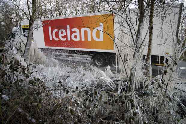 """An Iceland supermarket lorry passes a section of icicles and ice-covered hedgerow caused by a water splashed from the roadside near Hazeley Bottom, south of Reading, on March 27, 2013. Britain is in the grip of what the media has dubbed """"Miserable March"""", an unseasonal cold snap that threatens to bring the UK a White Easter. AFP PHOTO / ADRIAN DENNIS        (Photo credit should read ADRIAN DENNIS/AFP/Getty Images) TL"""