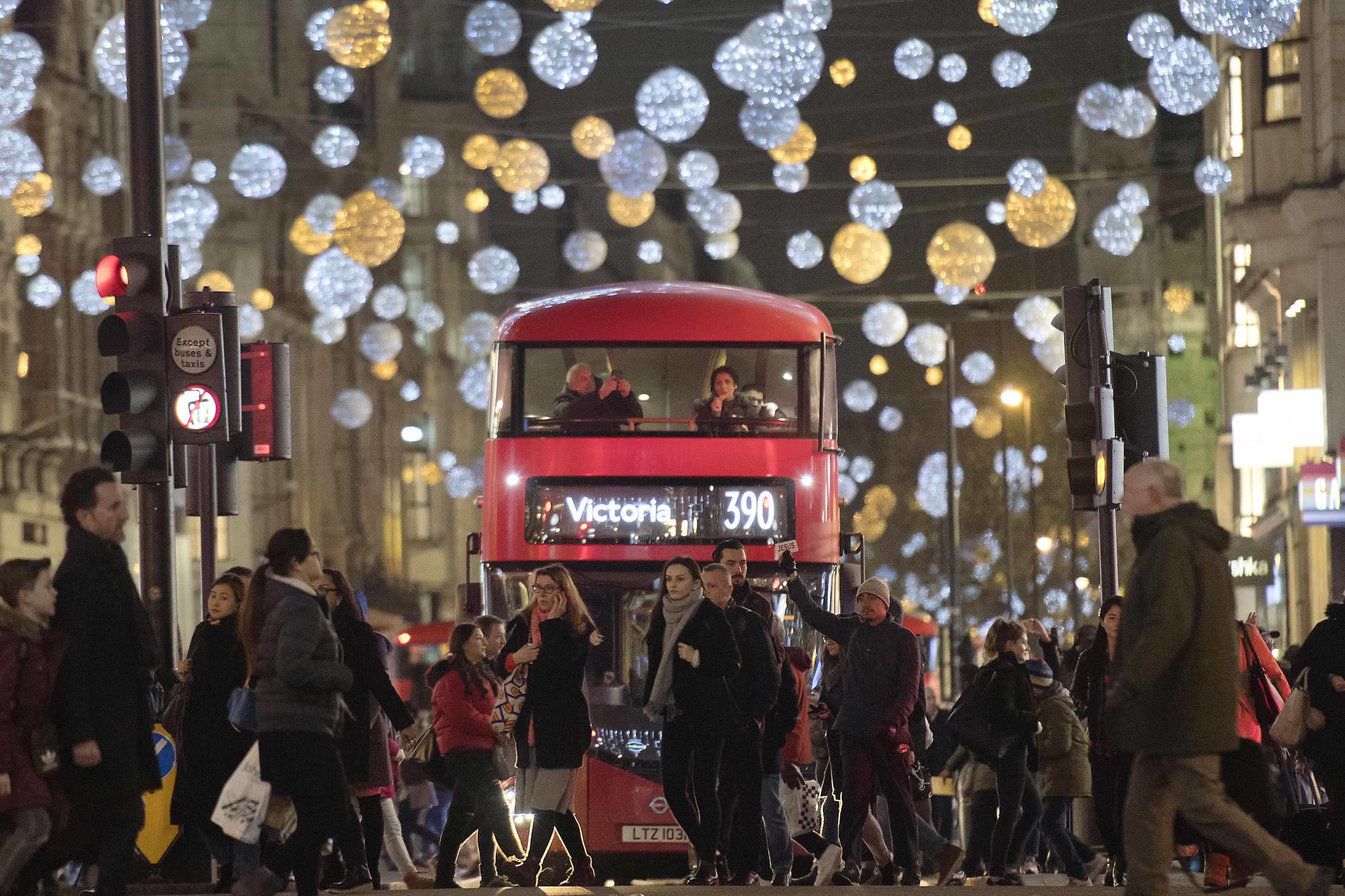 Shoppers cross in front of a London bus as it travels under Christmas lights on Oxford Street, in central London on December 5, 2017.  / AFP PHOTO / Justin TALLIS        (Photo credit should read JUSTIN TALLIS/AFP/Getty Images)