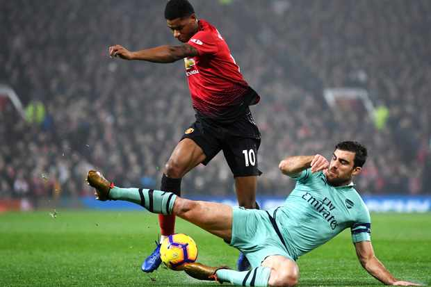 MANCHESTER, ENGLAND - DECEMBER 05:  Sokratis Papastathopoulos of Arsenal tackles Marcus Rashford of Manchester United during the Premier League match between Manchester United and Arsenal FC at Old Trafford on December 5, 2018 in Manchester, United Kingdom.  (Photo by Michael Regan/Getty Images)