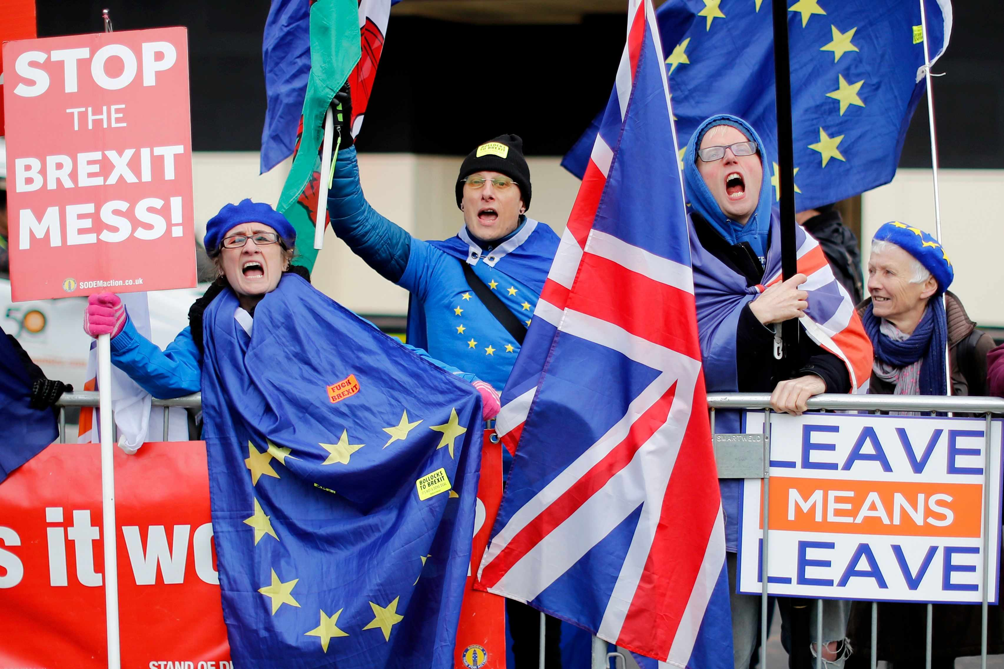 "Anti-Brexit supporters hold placards and flags as they demonstrate outside the Houses of Parliament on January 14, 2019. - Prime Minister Theresa May ramped up warnings today to MPs poised to reject her EU divorce deal that failing to deliver Brexit would be ""catastrophic"" for British democracy. (Photo by Tolga AKMEN / AFP)        (Photo credit should read TOLGA AKMEN/AFP/Getty Images)"