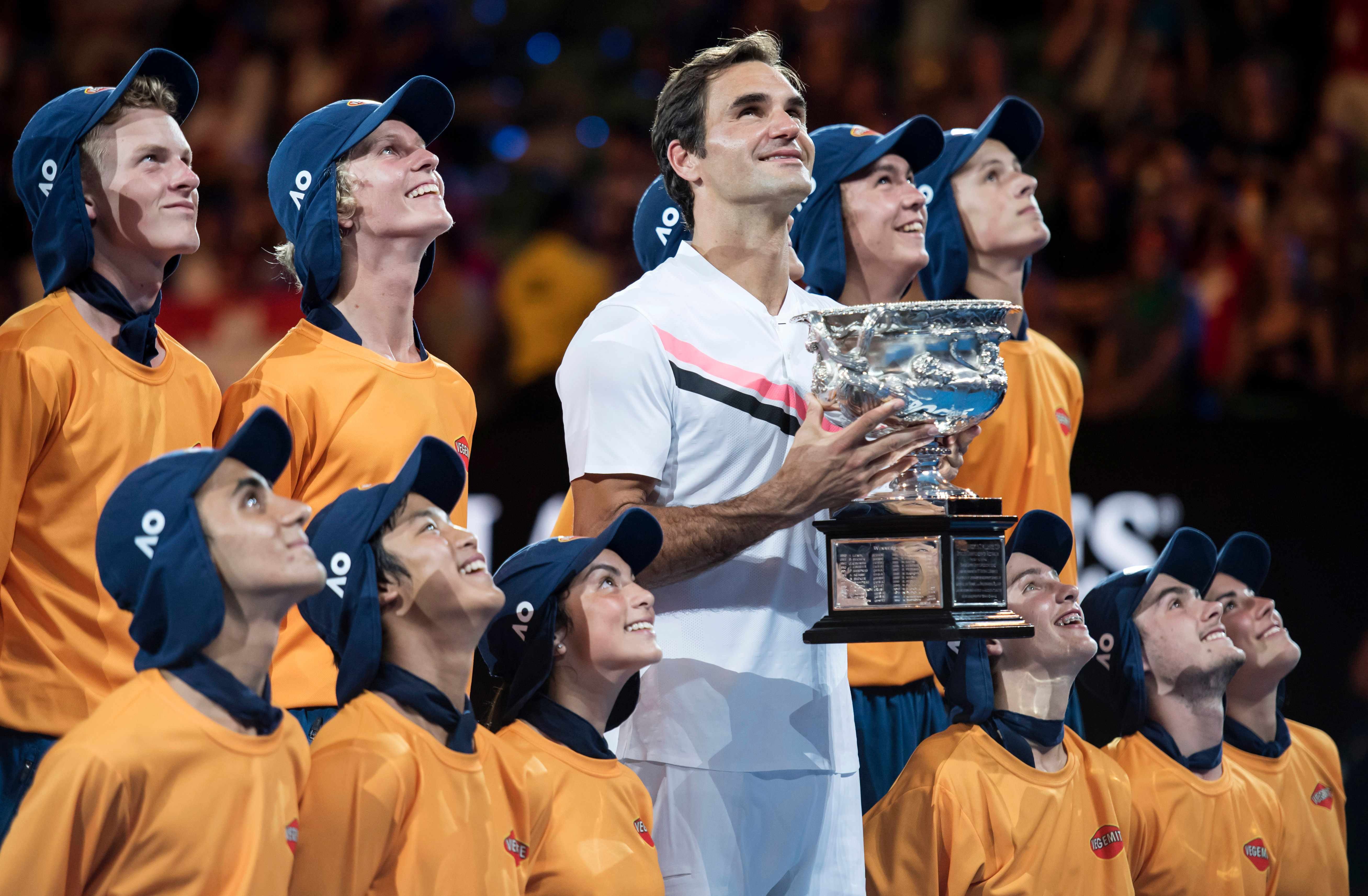 MELBOURNE, AUSTRALIA - JANUARY 28:  Roger Federer celebrates after winning the men's singles tournament against Marin Cilic of Croatia with the ball kids on day 14 of the 2018 Australian Open at Melbourne Park on January 28, 2018 in Melbourne, Australia.  (Photo by James D. Morgan/Getty Images)