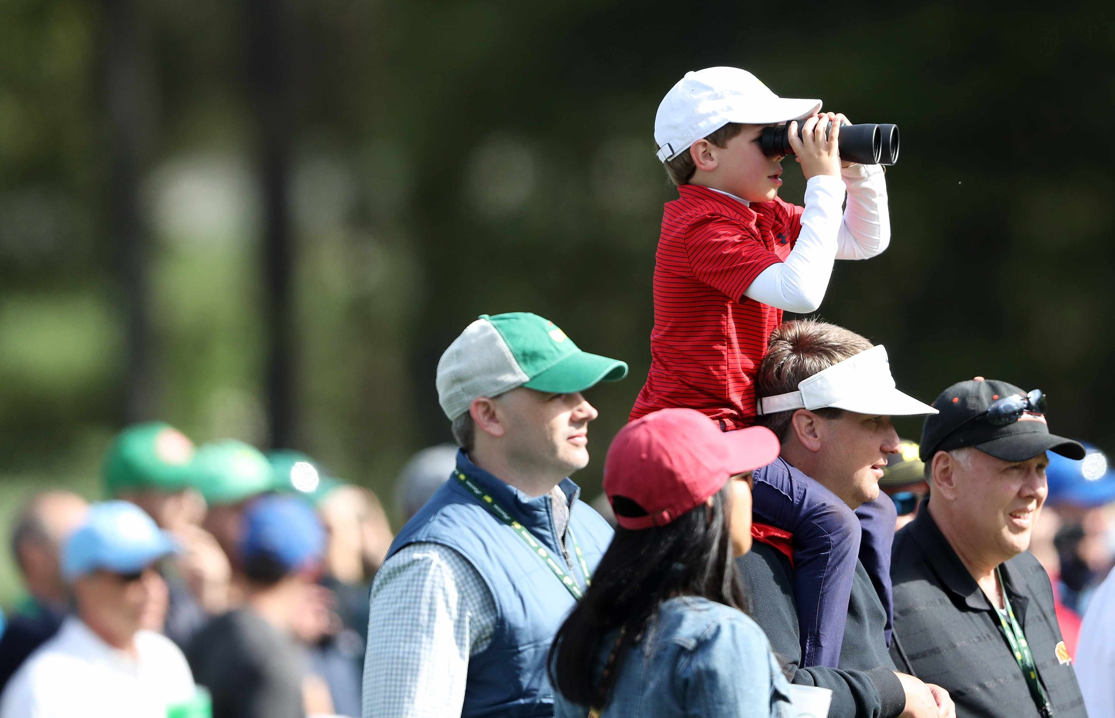 AUGUSTA, GA - APRIL 08:  A young patron uses binoculars to watch play during the final round of the 2018 Masters Tournament at Augusta National Golf Club on April 8, 2018 in Augusta, Georgia.  (Photo by David Cannon/Getty Images)