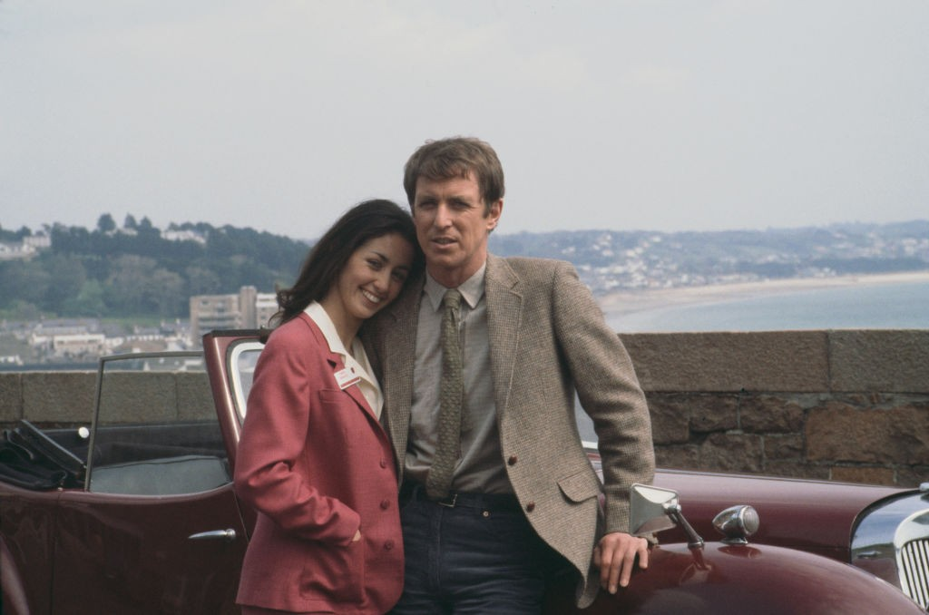 English actor John Nettles who appears in character as Jim Bergerac in the television drama series 'Bergerac', posed together with French actress Cecile Paoli on location during filming in the United Kingdom in 1981. (Photo by Larry Ellis Collection/Getty Images)